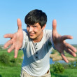 Cheerful guy with outstretched arms outdoors — Stock Photo