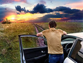Guy is standing near car and looking at the sunset — Stock Photo