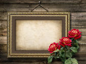 Old vintage frame for photos and a bouquet of red roses — Stock Photo