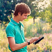 Young guy with a tablet outdoors — Stock Photo