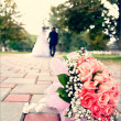 Bridal bouquet close up and blurred newlyweds — Stock Photo #33271945
