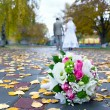 Bridal bouquet close up and blurred newlyweds — Stock Photo #34033417