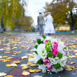 Stock Photo: Bridal bouquet close up and blurred newlyweds