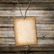 Vintage cardboard card on a rope. Wooden background — Stock Photo