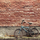 Old rusty vintage bicycle leaning against a brick wall — Stock Photo
