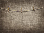Clothesline with clothespins on linen background — Stock Photo