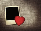 Polaroid-style photo and red paper heart on a linen background — Stock Photo