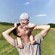 Father holds a small child on his shoulders — Stock Photo #50147409