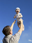 Father tossing baby in the air — Stock Photo