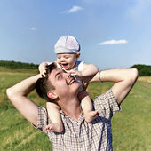 Father holds a small child on his shoulders — Stock Photo