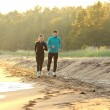 Young man and woman running along the waterfront — Stock Photo