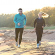 Young man and woman running along the waterfront — Stock Photo #20614827