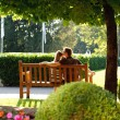 Young couple sitting on a bench in the park — Stock Photo