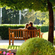 Young couple sitting on a bench in the park — Stock Photo #24624537
