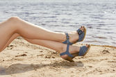 Woman feet in sandals on the beach — Stock Photo