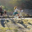 Two girls riding a bike in the park — Stock Photo