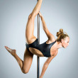 Young sexy woman exercise pole dance against a gray background — Stock Photo