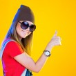 Portrait of funny girl in glasses and a brown hat. Smiling and looking at viewer. Thumb up. Isolation on a yellow background. — Stock Photo