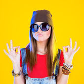 Portrait of funny girl in glasses and a brown hat. Seriously looking at viewer. Everything is ok. Isolation on a yellow background. — Stock Photo
