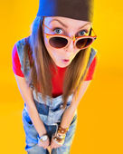 Portrait of funny girl in glasses and a brown hat. Stares at the viewer. Isolation on a yellow background. — Stock Photo