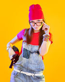 Portrait of funny girl in glasses and red caps. Seriously looking at viewer. Isolation on a yellow background. — Stock Photo