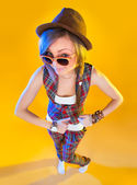 Funny girl in full growth in glasses and a brown hat. Fun dancing and looking at viewer. Isolation on a yellow background. — Stock Photo
