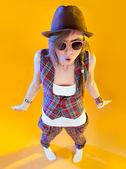 Funny girl in full growth in glasses and a brown hat. Throws up his hands in surprise and looking at viewer. Isolation on a yellow background. — Stock Photo