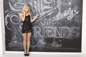 Girl standing at the blackboard with chalk on which is written the word friends — Stock Photo