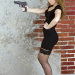 Girl with a gun against a brick wall — Stockfoto