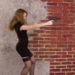 Portrait of a young girl in a black dress and stockings against a brick wall — Stock Photo #12720473