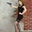 Girl with a gun against a brick wall — Foto de Stock