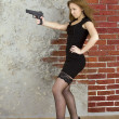 Girl with a gun against a brick wall — 图库照片