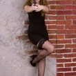 Portrait of a young girl in a black dress and stockings against a brick wall — Stock Photo