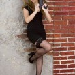 Portrait of a young girl in a black dress and stockings against a brick wall — 图库照片