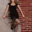 Stock Photo: Portrait of a young girl in a black dress and stockings against a brick wall