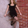 Portrait of a young girl in a black dress and stockings against a brick wall — Stockfoto