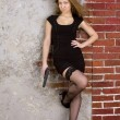Girl with a gun against a brick wall — Lizenzfreies Foto