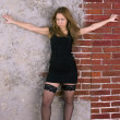 Portrait of a young girl in a black dress and stockings against a brick wall — Foto de Stock