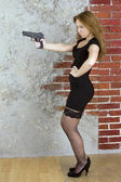 Girl with a gun against a brick wall — Stock Photo