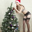 Girl in lingerie and stockings dress up a Christmas tree — Stock Photo