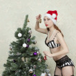 Girl in lingerie and stockings dress up a Christmas tree — Stock Photo #15851977