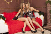Two girls sitting on a red couch — Stock Photo
