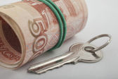 The key to the apartment, which lies next to a bundle of money — Foto Stock