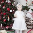 Stock Photo: Little girl stands urozhdestvenskoy tree