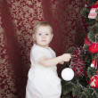 Little girl decorates a New Year tree — Lizenzfreies Foto