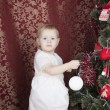 Little girl decorates a New Year tree - Stock Photo