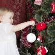 Little girl decorates a New Year tree — Foto de Stock