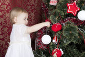 Little girl decorates a New Year tree — Zdjęcie stockowe