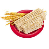 Grain bread and ears of wheat lying in the red plate isolated on white background — Stock Photo