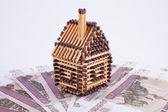 House made of matches is on a fan of banknotes — Foto Stock